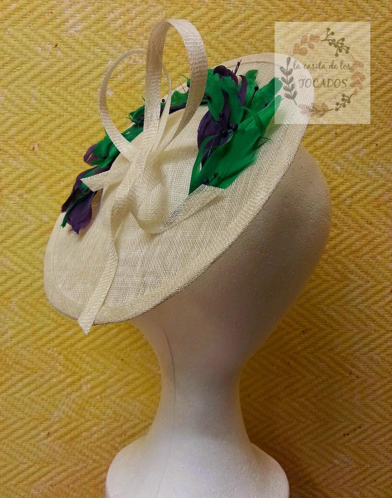 tocado mediano para boda de mañana con base de sinamay en crudo y plumas mezcladas en verde y morado además de pistilos pintados