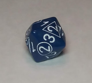 An oddly-shaped chunk of blue plastic. It has a variety of numbers between 1 and 4 printed on it in white, some of those numbers in a circle or a triangle. The die is shaped such that whenever it lands, a number with no shape will land on top, and beside that number is one number in a circle, and one number in a triangle.
