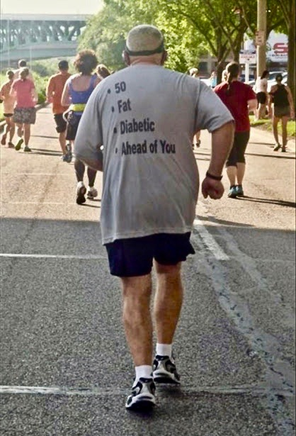 Photo of man jogging in a community race. Back of shirt reads 50. fat. diabetic. ahead of you. Stories of Voluntary Exercise. Perils of jogging. marchmatron.com