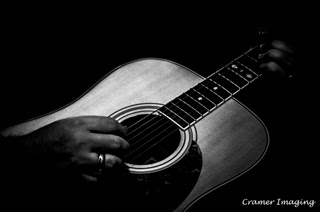 Cramer Imaging's professional quality fine art music low key black and white photograph of hands strumming an acoustic guitar