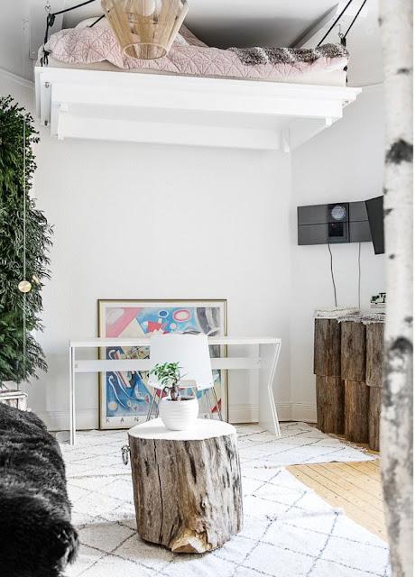 Pat suspendat pe scripeți și un perete cu crengi de brad într-o garsonieră de 29 m²