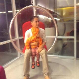 Ayah dan anak duduk di kursi gantung
