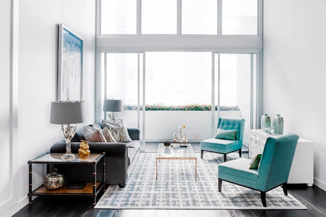 Bright, modern living room in Sydney, Australia by Brendan Wong wit ha geometric patterned rug, dark wood floor, floor to ceiling windows, and turquoise chairs