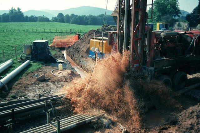 Hardthorn Road site, Dumfries, Dumfries and Galloway Region. Water strike during drilling for groundwater at Hardthorn Road.   The rotary drilling rig encountered only dry Permian breccia to 56 m. depth. At this level, a water-bearing fissure suddenly produced a surge of water at the surface. Other fissures were encountered at intervals to 130 m. depth. The final yield of water from the borehole was over 35 litres per second. The borehole is to be used by West of Scotland Water as part of the Dumfries public supply system. The Silurian hills can be seen in the background. These encircle the Permian aquifer in the floor of the basin.