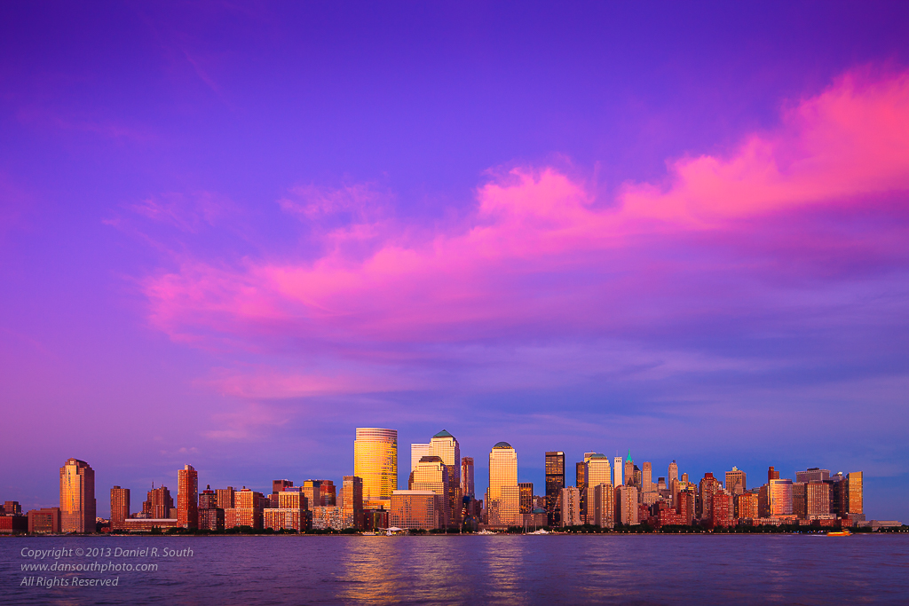 a photo of the new york skyline under pink clouds