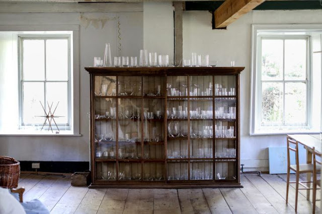 Farmhouse dining room with glass front cabinets full of crystal and glassware - found on Hello Lovely Studio