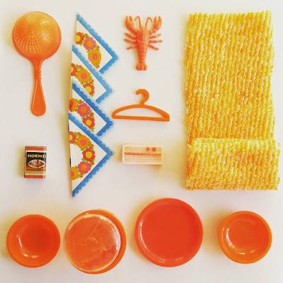 Flatlay of vintage dolls' house miniatures in orange colours.