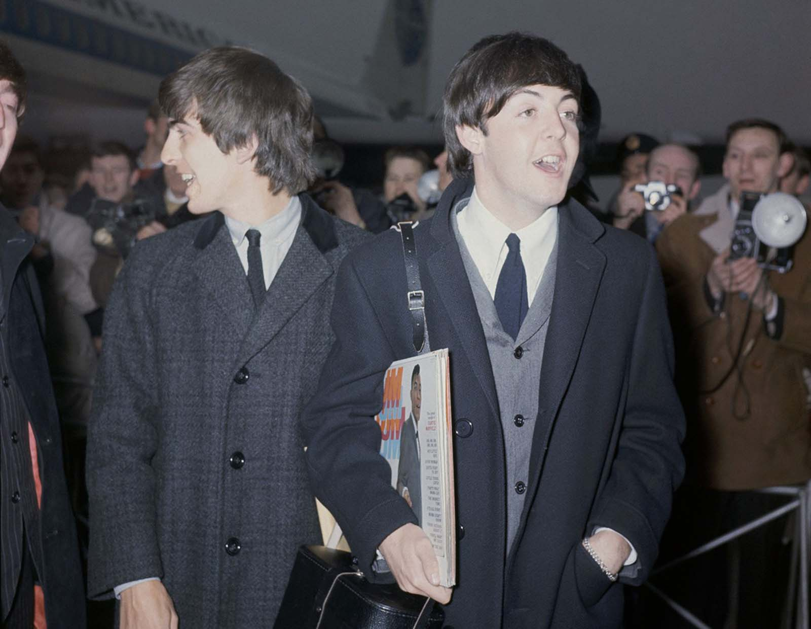 The Beatles arrive at London Airport, England, February 22, 1964, after their visit to the United States. In the foreground is Paul McCartney, carrying record albums under his arm (including