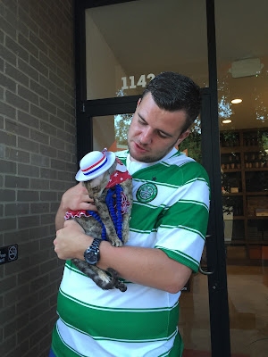 Coco the Couture Cat being held by a man at a pub
