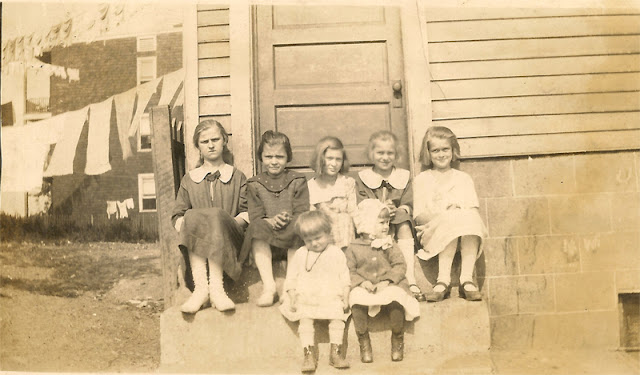 Seven unidentified girls sitting on a stoop. Maybe 1920's. Ages from toddler to early teens.
