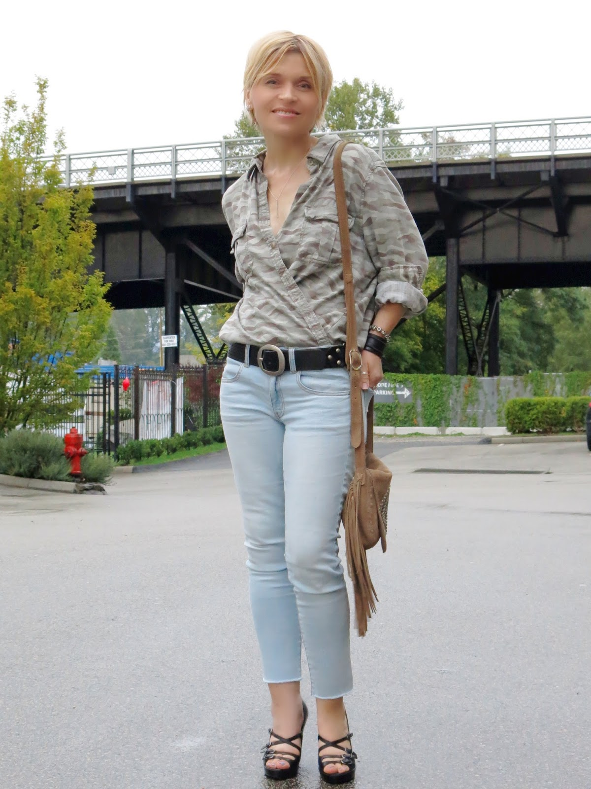 styling an oversized camo shirt with skinny jeans, strappy shoes, and a fringy Steve Madden bag