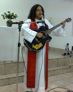 Rev. Borges standing on a platform, she is wearing a pastor's robe with a red stole, and playing a guitar.