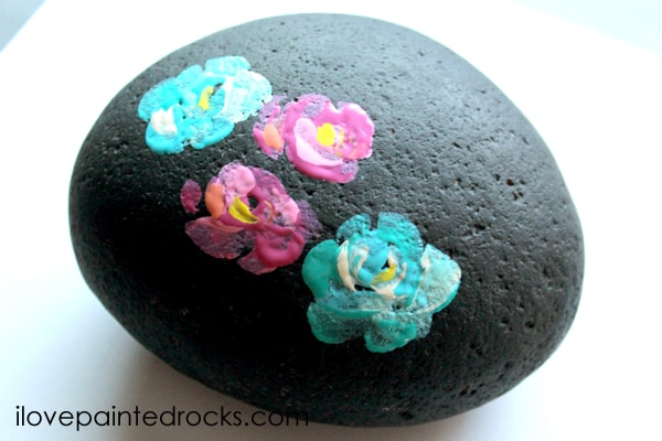 pink and blue flowers on a painted rock