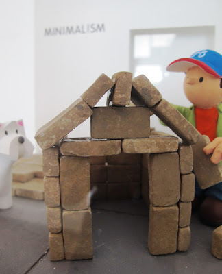 Miniature clay figure, building a dog house out of bricks in a gallery, with a dog looking on.