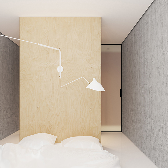 Bedroom with bed on floor and large white wall sconce. Gorgeous small minimalistic apartment by Emil Dervish