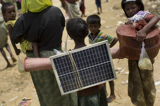 A Rohingya Muslim child carries a solar panel as she crosses over the border