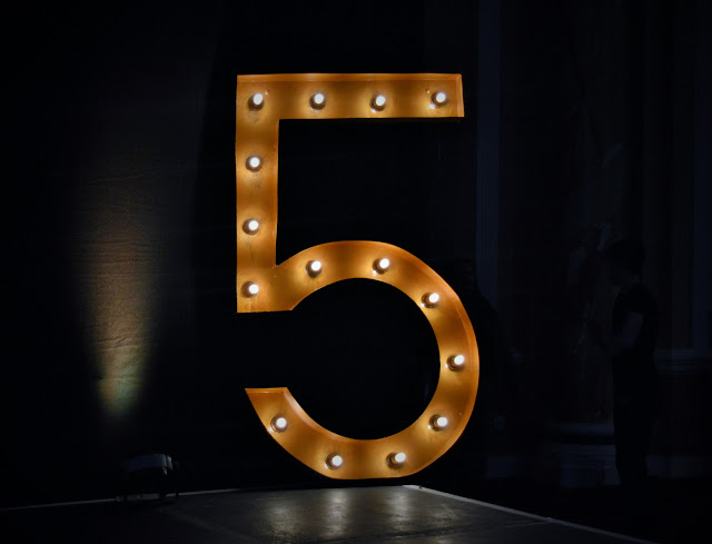 A black stage with a giant five in lights upon it.