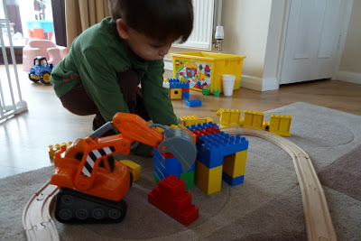 Child playing with Lego and digger