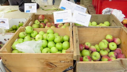 Wooden bins of 4 early apples at farmers market