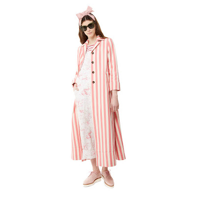 A girl in a pair of floral dungaress and a striped pink coat.