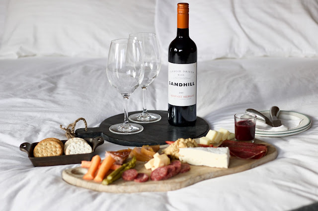Charcuterie board on bed with Sandhill Wine Bottle