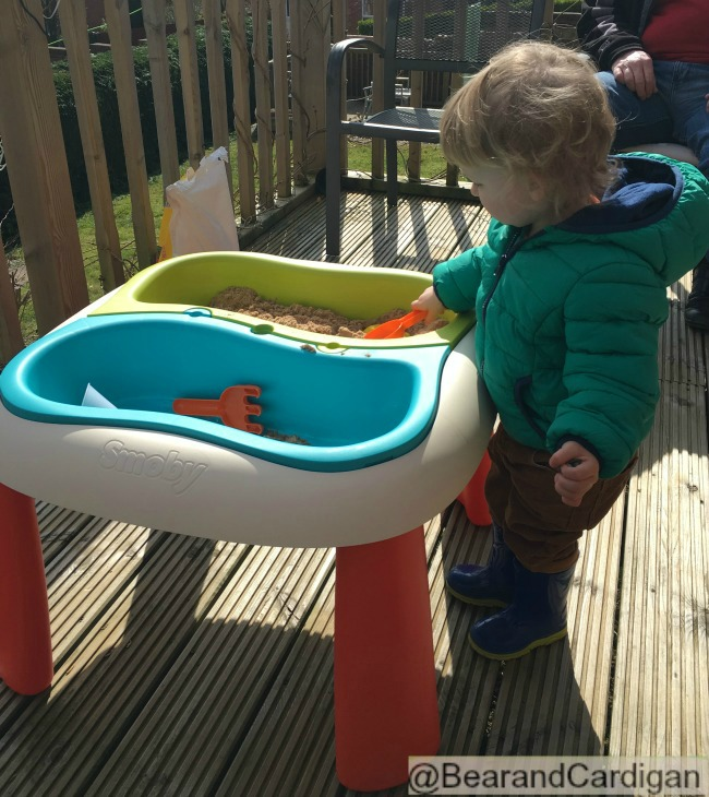 A Very Quiet Week. Just Sand and Water. toddler playing with sand in a tray on decking