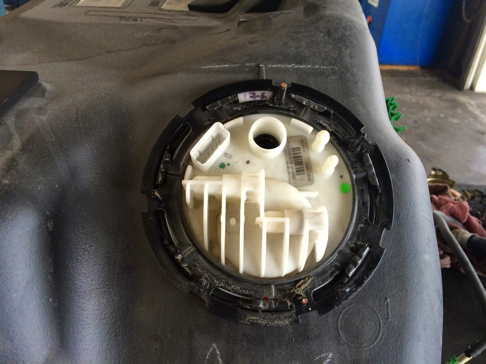With a BRASS punch remove the metal holder. Use brass you don't want to  create sparks close to the fuel tank. Use safety goggles!!!