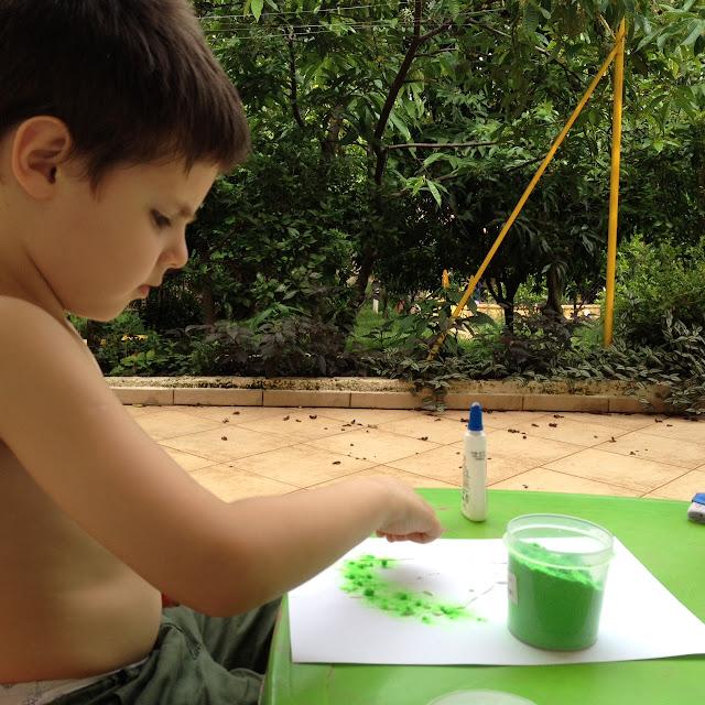 Imagem do Miguel brincando com papel, cola e pó de flocagem