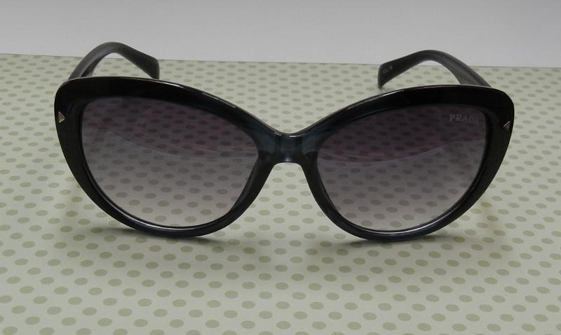 5c50f5b05683d ... são óculos escuros retrô no estilo gatinho originais da marca Prada. A  armação é preta e azul petróleo e a ponta das hastes são roxas.