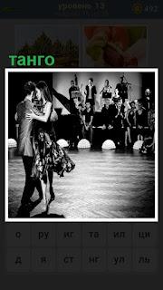 мужчина и женщина исполняют танго перед зрителями