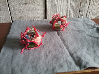 Two pin cushions, each made of 6 square calico pillows, joined at the corners to make a hollow ball. Each vertex tied with a pink bow.