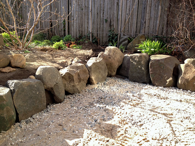 Reclaimed slate backyard patio Artist and Builder setting stones to fit is fun