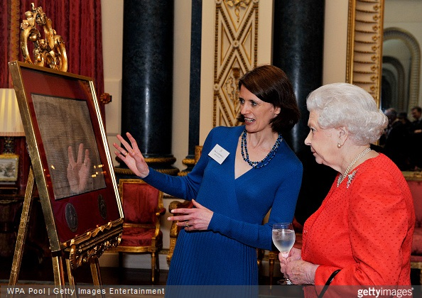 Queen Elizabeth looks on as she is shown a copy of the magna carta by Dr Claire Breay of the British Library during a reception to mark the 800th anniversary of the Magna Carta at at Buckingham Place