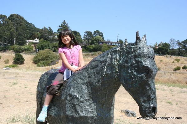 child astride statue in Blackie's Pasture in Tiburon, California