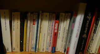 das Bild zeigt sehr viele dünne Bücher in einem Regal