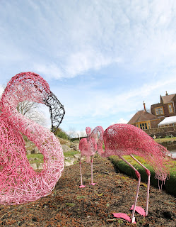 Three large pink wire flamingo sculptures outside in the garden, one in the foreground of the shot. Blue sky and buildings are visible in the background