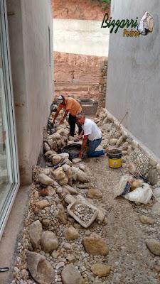Dia 19 de setembro de 2016, Bizzarri orientando e ajudando na execução do lago ornamental com pedra do rio e pedregulho do rio em jardim de inverno na sala de estar em residência no condomínio em Atibaia-SP.