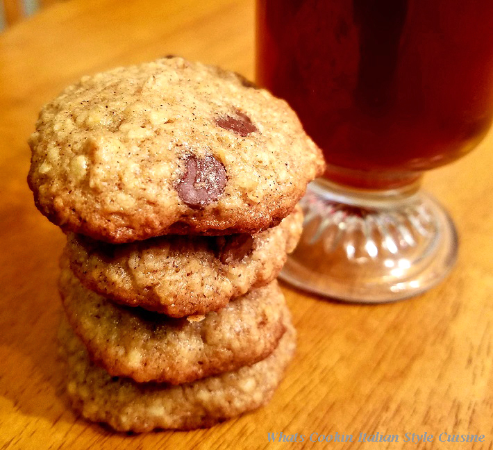 this is a basic oatmeal cookie recipe that can be changed into anything you want when adding ingredients. These are a chocolate chip oatmeal cookie with a clear coffee mug filled with coffee in the background.