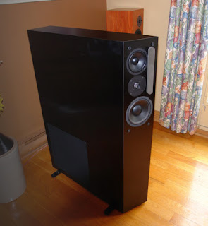 image of black NHT 3.3 speakers inside a room with many wood accents.