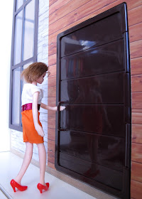 A doll opening the front door of the modern Lori Loft to Love dolls' house.