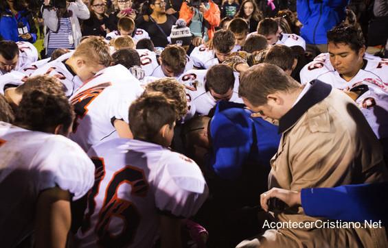 Entrenador de fútbol americano orando con jugadores en escuela
