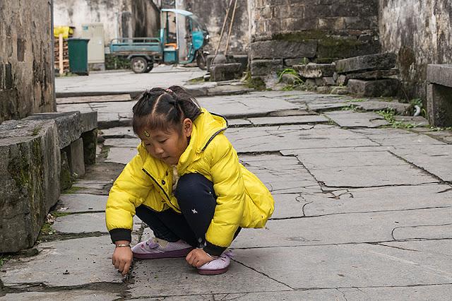 Petite fille chinoise s'amusant dans une ruelle de Xidi