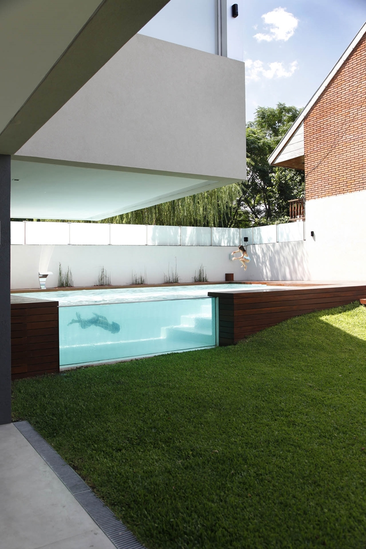 Kids jumping into the pool in Modern Villa Devoto by Andres Remy Architects