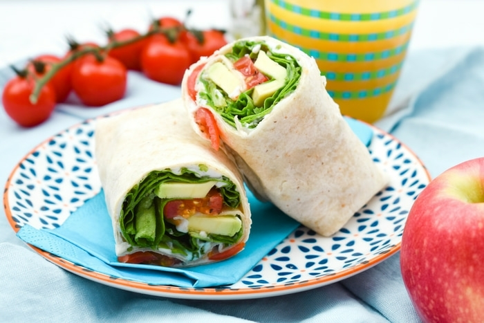 Green Power Lunch Wrap. A lush green lunchtime wrap featuring spinach and creamy avocado with a tangy dressing. Delicious! Includes calories, nutrition and a free printable recipe.
