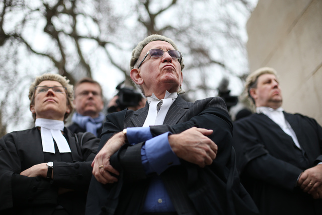 A photo of several British advocates, arms folded, looking grumpy. Photo was taken from below, looking up.  All male advocates (whether barrister or solicitor) wear a white stiff wing collar with bands. Court Complexities and Legal Fiction, A Moron In A Hurry marchmatron.com