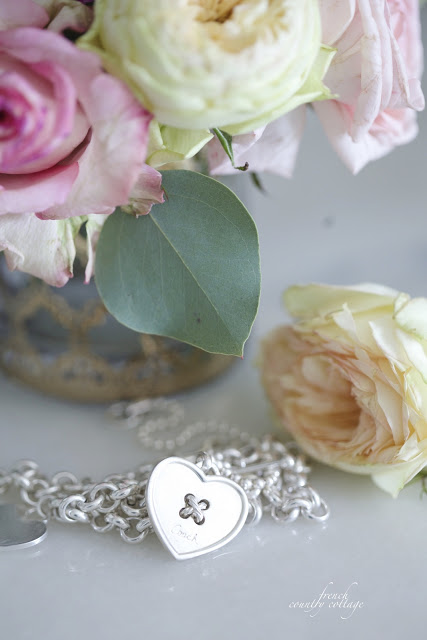 silver necklace on a counter with flowers