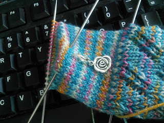 A close of up the heel flap of the socks.  The heel flap is an eye-of-partridge heel, with a silver rose stitch marker marking the centre of the heel. The yarn is blue with flecks of other colours.