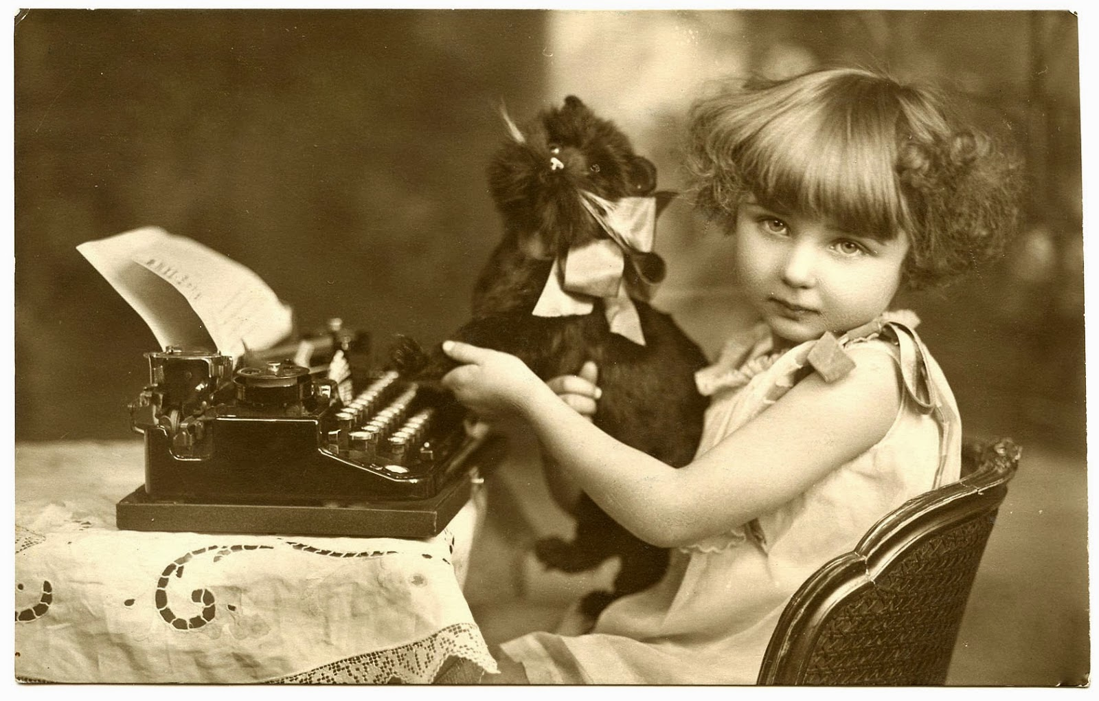 Vintage image of girl and cat plushy in front of typewriter.