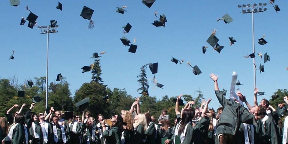 Pós-graduandos jogando quepes para o alto