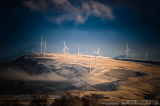 Cramer Imaging's fine art landscape photograph of wind turbines on hill in golden light of sunset just after winter snow storm
